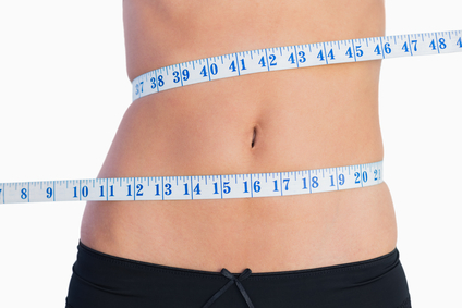 Fit belly surrounded by measuring tape on white background